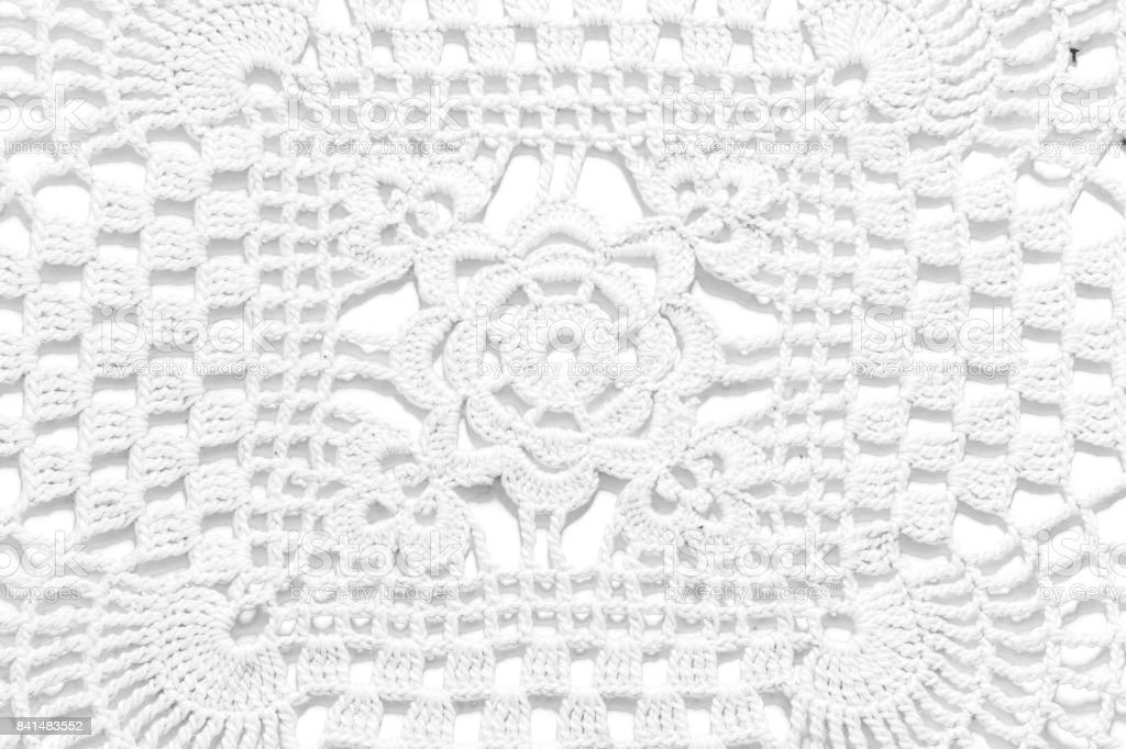 White handmade lace tablecloth texture on white background stock photo