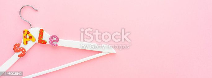 Creative top view flat lay white wooden hangers sale text pastel pink background copy space minimalism style. Template fashion feminine social media sale children store promo design shopping banner