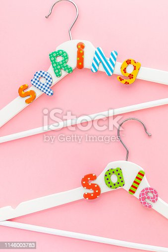 Creative top view flat lay white wooden hangers sale text pastel pink background with copy space minimalism style. Template fashion feminine blog social media sale store promo design shopping concept