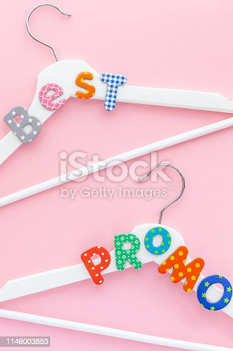 Creative top view flat lay white wooden hangers best promo text pastel pink background with copy space minimalism style. Template fashion feminine blog social media sale store design shopping concept