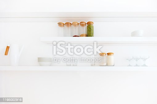 839034546 istock photo white hanging shelves in contemporary kitchen in eco style 1195002916