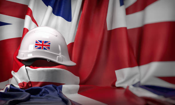 White hard hat laying over UK  flag. Construction and employment in United  Kingdom UK concept, Labor day. stock photo