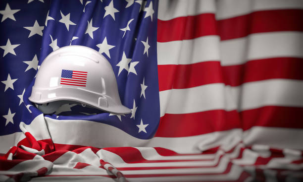 White hard hat laying over USA flag. Construction and employment in United States USA concept, Labor day stock photo