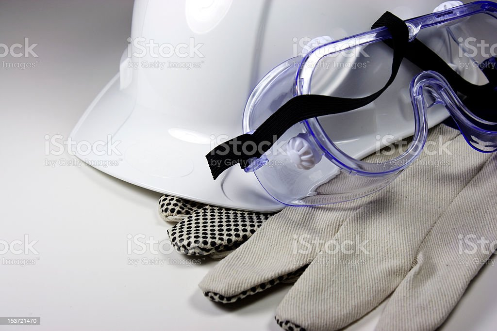 White hard hat plastic goggles and protective gloves stock photo