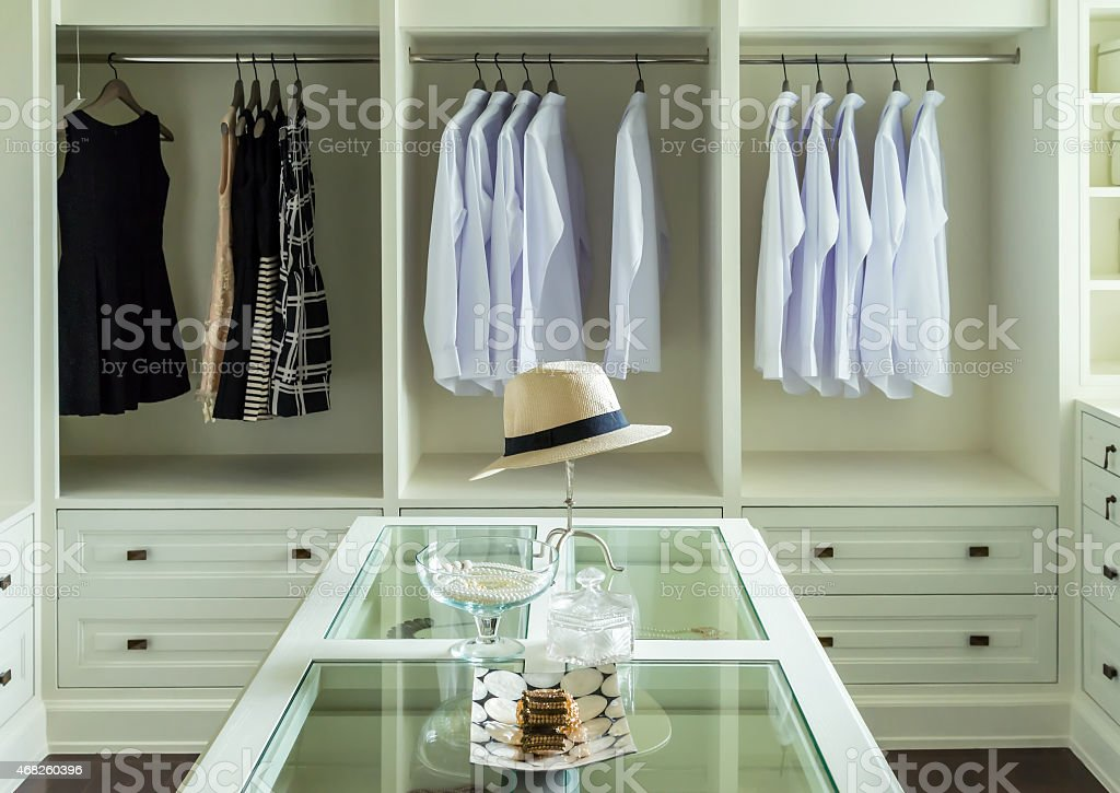 white hat and jewelry set on a dresser table stock photo