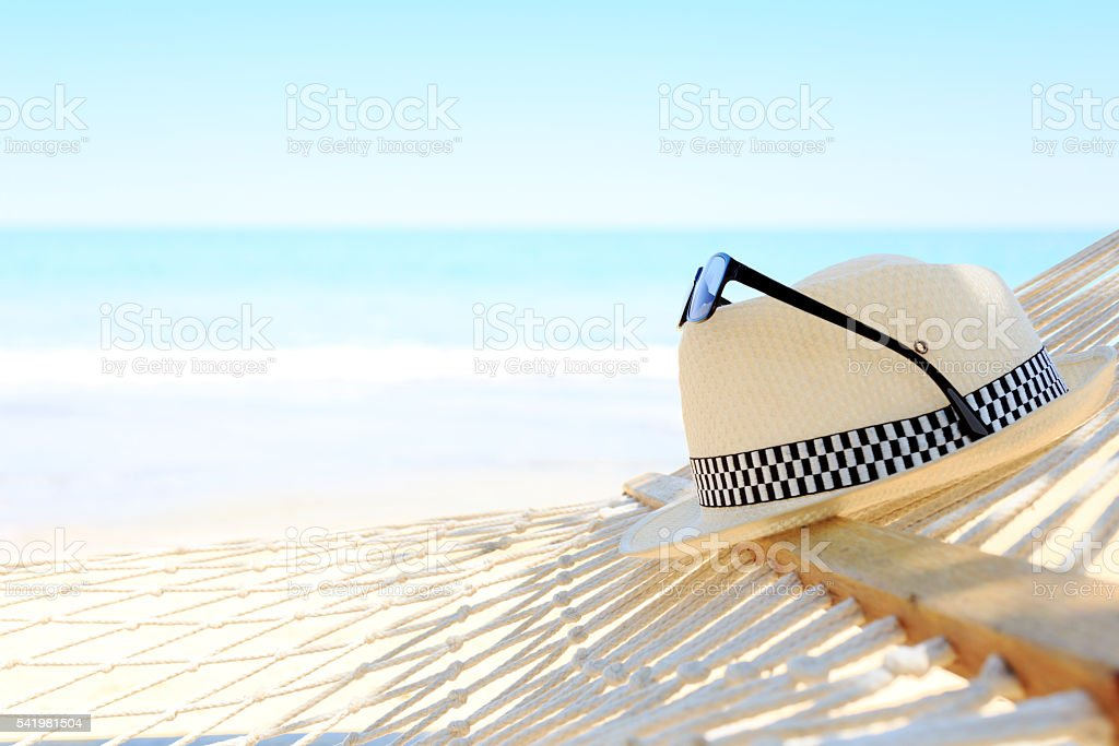White hat and sunglasses with hammock on Beach view summer stock photo