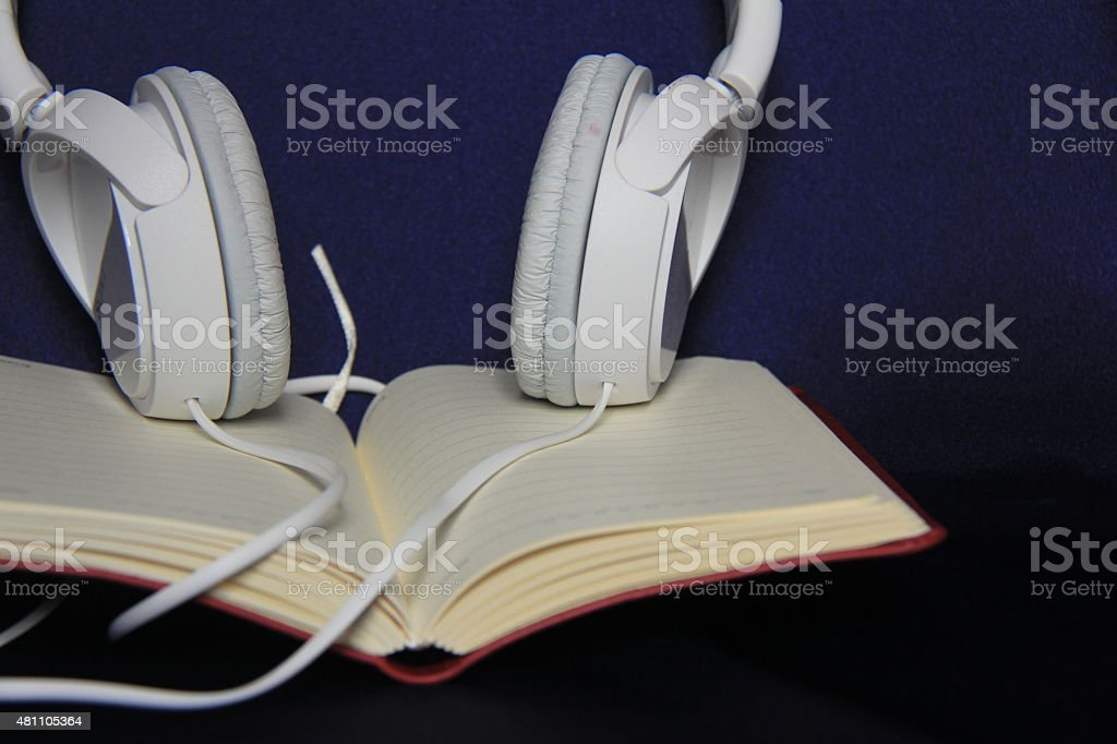 White headphone on top of the book stock photo
