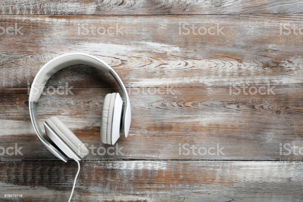 White headphones on a brown wooden table royalty-free stock photo