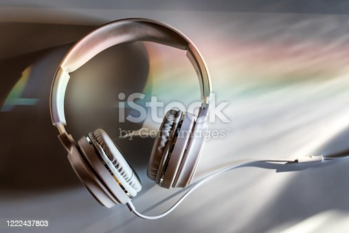 White Headphones On A White table lit by a sunset light dispersed into rainbow. Headphones at the office desk top at the end of the day