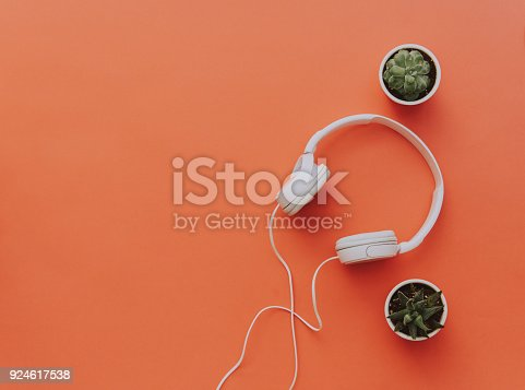 istock White headphones on orange background with cactus. Minimal blogger or music background 924617538