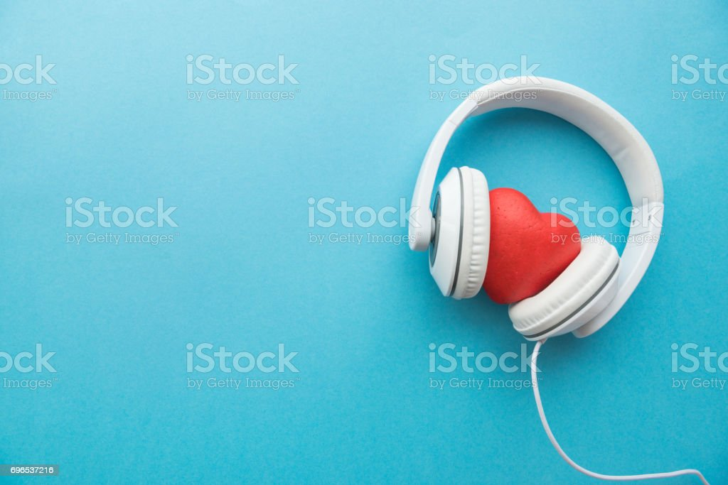 White headphones with red heart sign in the middle on blue surface stock photo