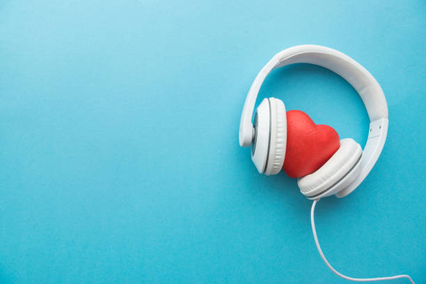 white headphones with red heart sign in the middle on blue surface - music stock photos and pictures