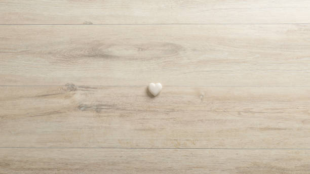 White heart made of stone lying on a woodenk desk stock photo
