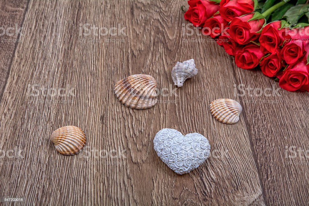 White heart, roses and shells on a wooden background stock photo