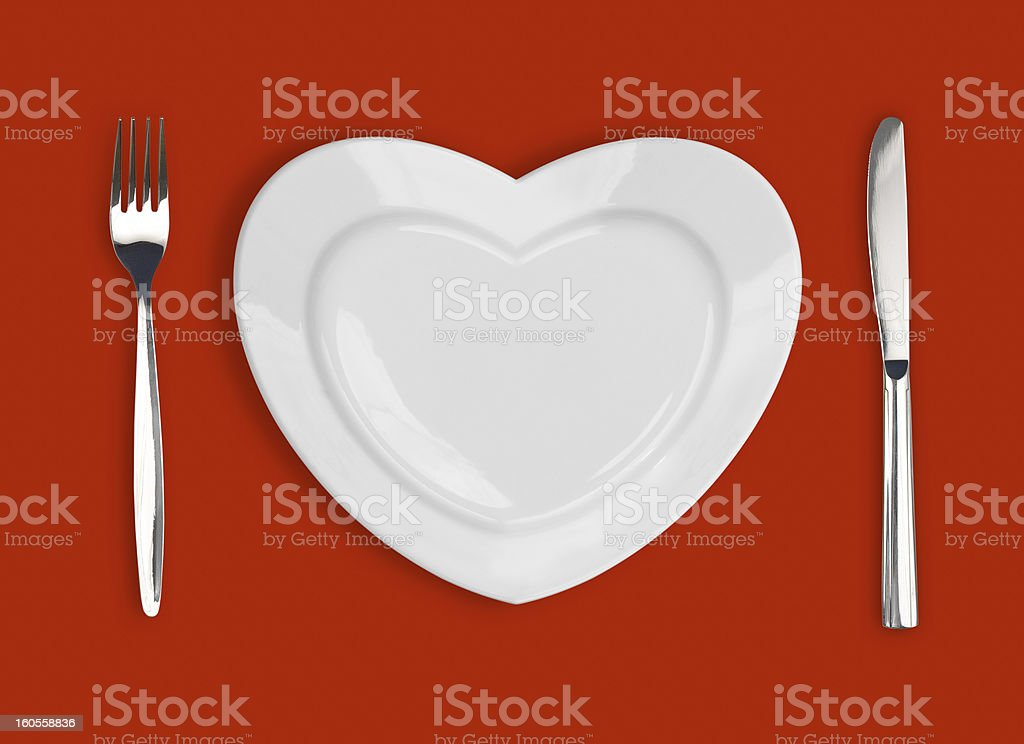 White heart shaped plate with silverware on a red mat royalty-free stock photo