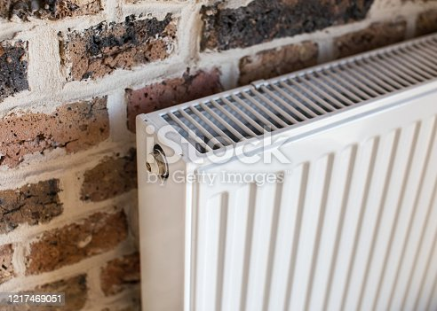 White heater radiator hanging on a brick wall