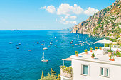 white holiday villa with balcony and rooftop terrace facing Mediterranean sea with mountains at background on sunny summer day, Positano, Amalfi coast, Italy