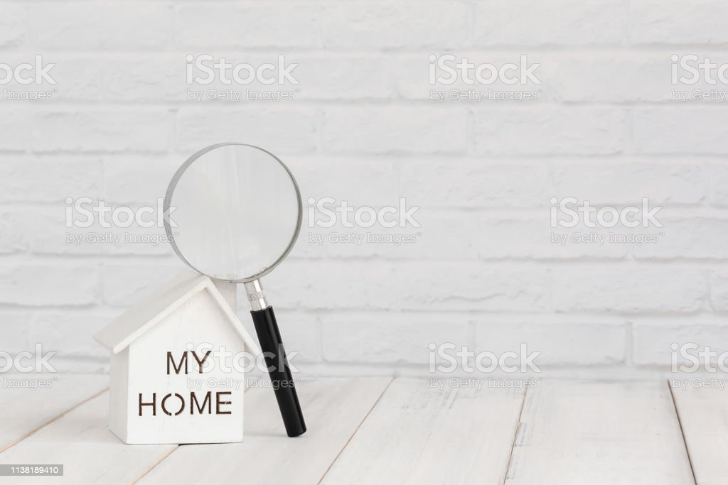 White home and magnifying on white wood table over white brick...