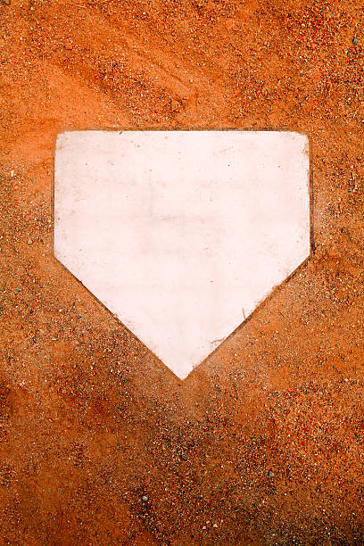 White home plate set in orange sand stock photo