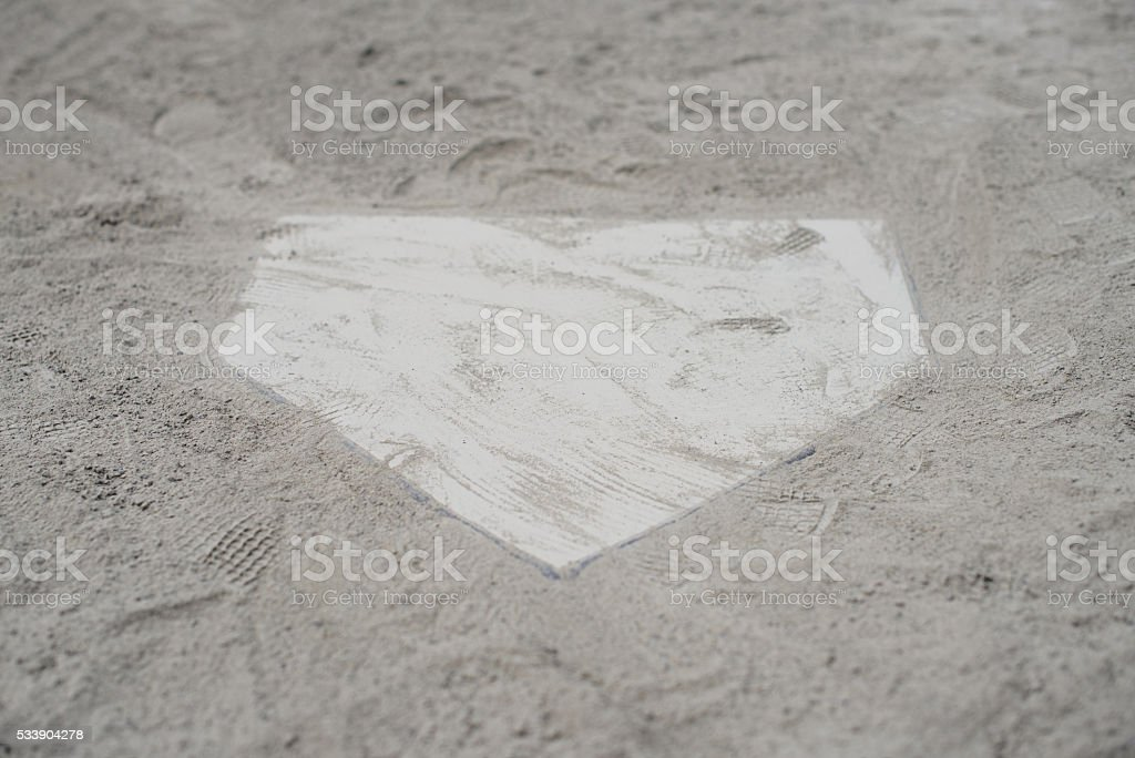 White home plate set in sand stock photo