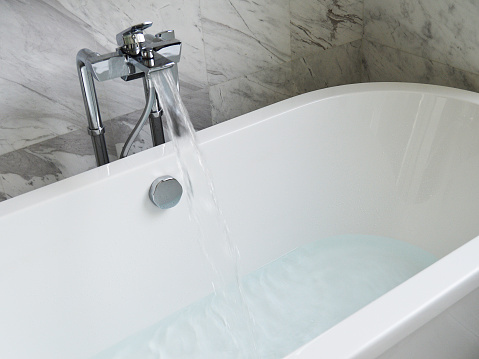 White, clean hotel bathtub and running water faucet