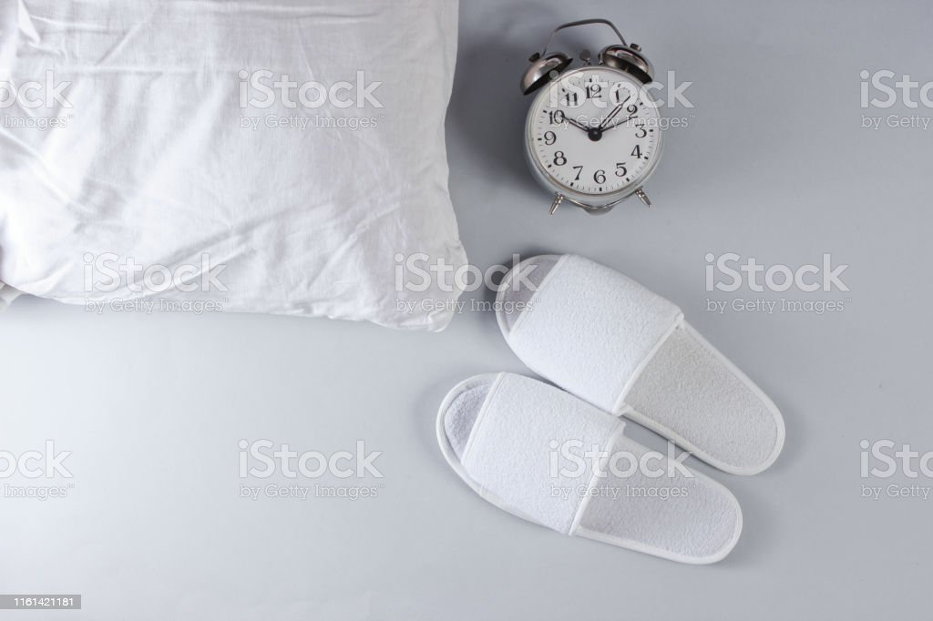 https www istockphoto com photo white hotel sleeping slippers alarm clock and pillow on gray background time to gm1161421181 318250646