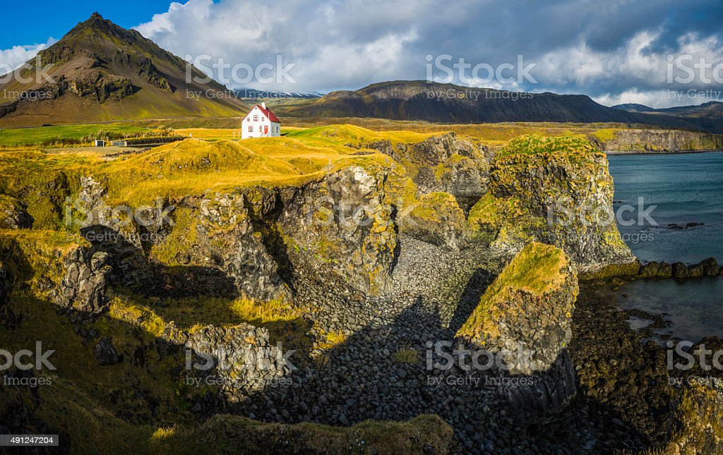 White house on dramatic rocky shore ocean mountain Snaefellsnes Iceland stock photo