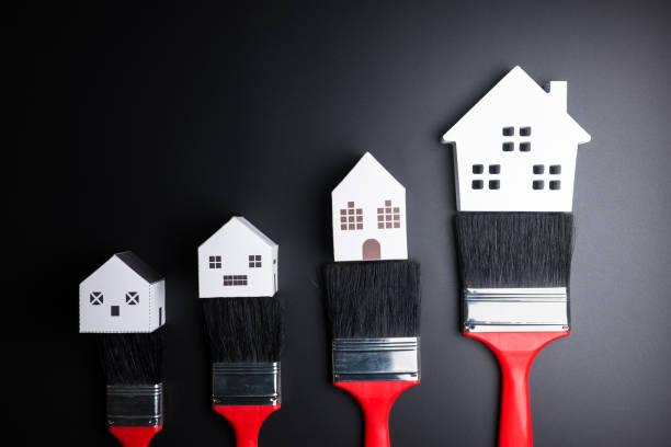 Weiße Haus Spielzeug und Farbe Pinsel auf schwarzem Hintergrund mit Textfreiraum. Immobilien-Konzept, neues Haus-Konzept, Finanzen Kredit Geschäftskonzept, Reparatur Wartungskonzept. – Foto