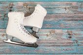 White ice skated for women on a blue wooden background