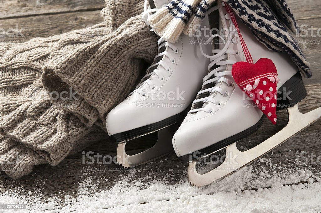 White ice skates on old wooden boards stock photo