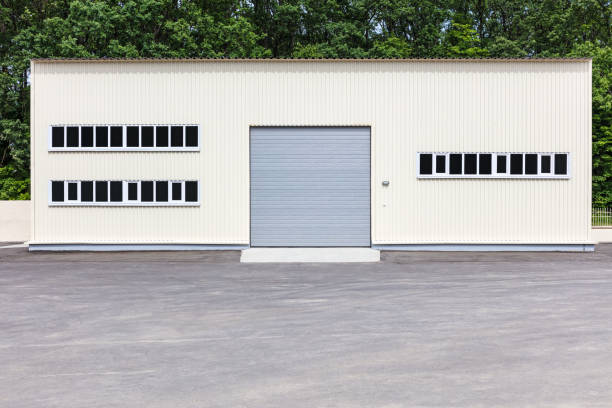 white industrial building facade with grey roller shutter gate stock photo