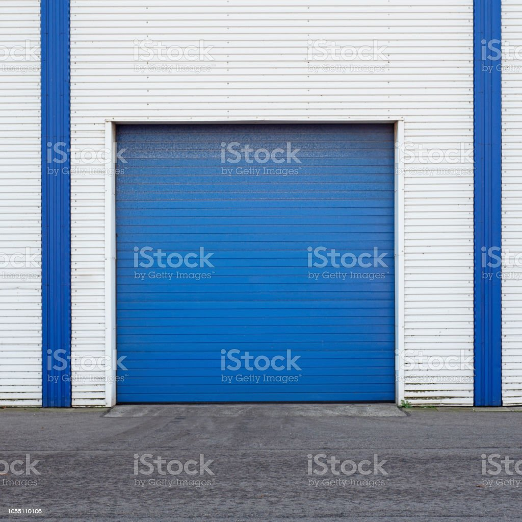 White Industrial warehouse with blue door for trucks. stock photo