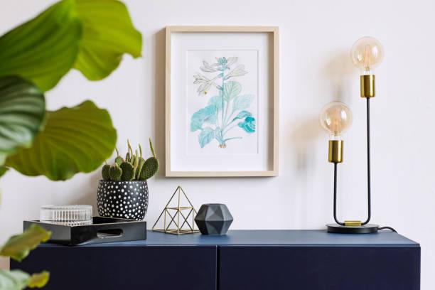 intérieur blanc d'affiche floral mock up avec armature en bois vertical, lampe de table, cactus, pyramide or et fleurs tropicales sur le fond de mur blanc. concept avec étagère bleu marine. - camera sculpture photos et images de collection