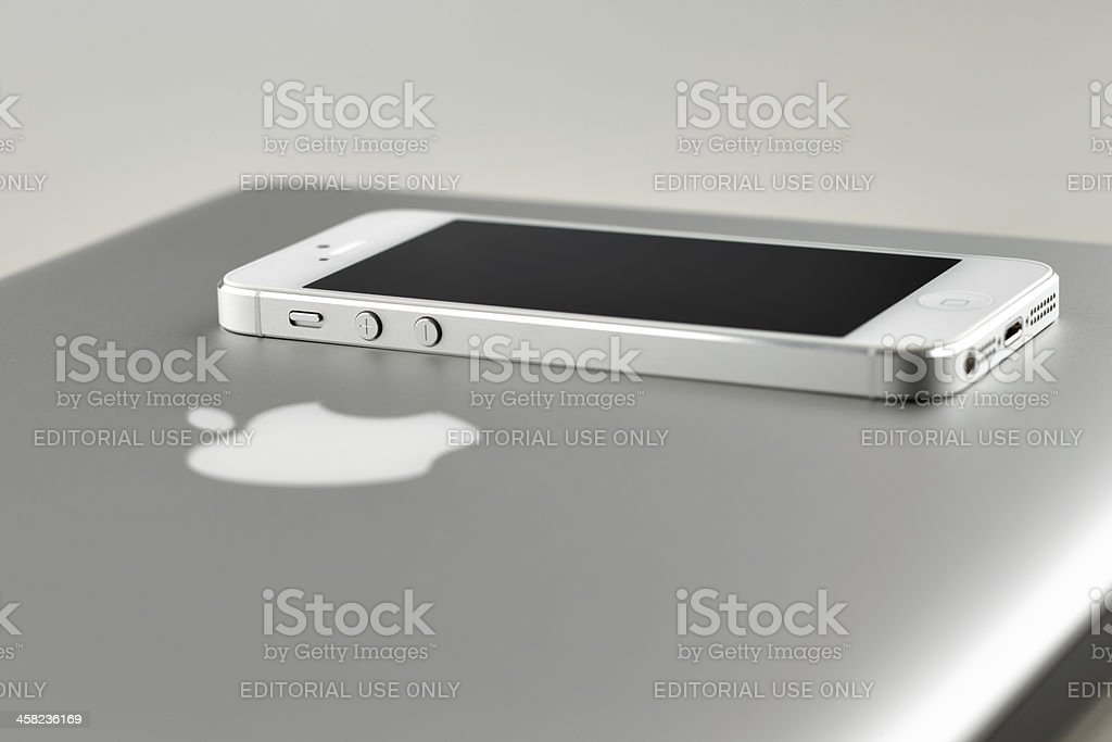 White iPhone 5 laying on Apple MacBook Pro laptop computer royalty-free stock photo