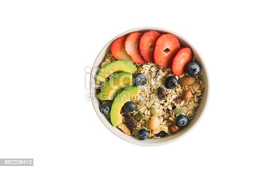 istock White isolated background with clipping paths muesli or granola on white bowl top with fresh blueberries, strawberries and avocado for breakfast in top view flat lay. Healthy food concept. 882208410