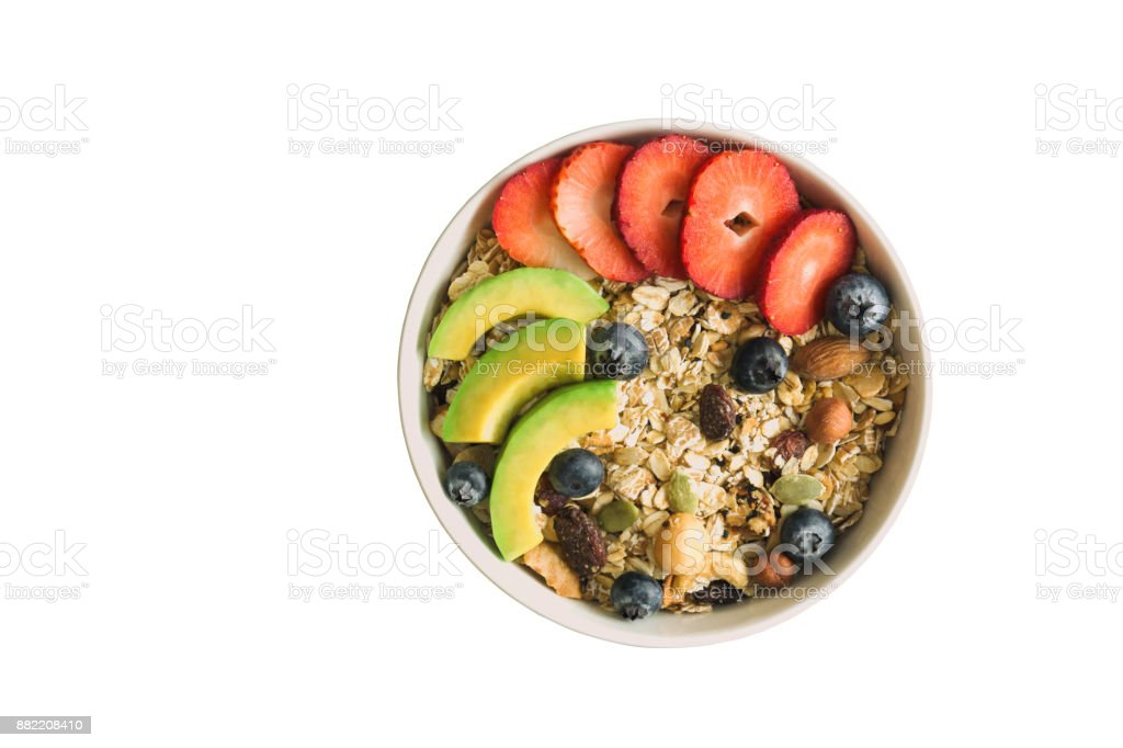 White isolated background with clipping paths muesli or granola on white bowl top with fresh blueberries, strawberries and avocado for breakfast in top view flat lay. Healthy food concept. stock photo