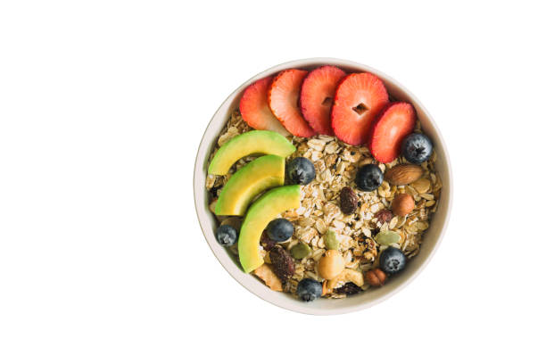 white isolated background with clipping paths muesli or granola on white bowl top with fresh blueberries, strawberries and avocado for breakfast in top view flat lay. healthy food concept. - oats food stock photos and pictures
