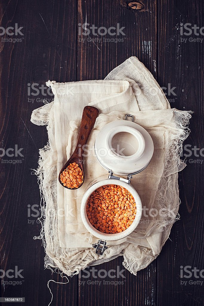 White jar and spoon with red lentils on wood background royalty-free stock photo