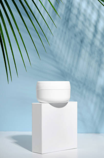White jar of cream on a stand on a blue background with tropical palm leaves and their shadow. Stylish look of the product, mock up, identity. stock photo