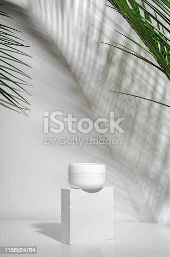 istock White jar of cream on a stand on a white background with tropical palm leaves and their shadow. Stylish look of the product, mock up, identity. 1156524784