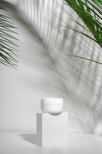 White jar of cream on a stand on a white background with tropical palm leaves and their shadow. Stylish look of the product, mock up, identity. stock photo