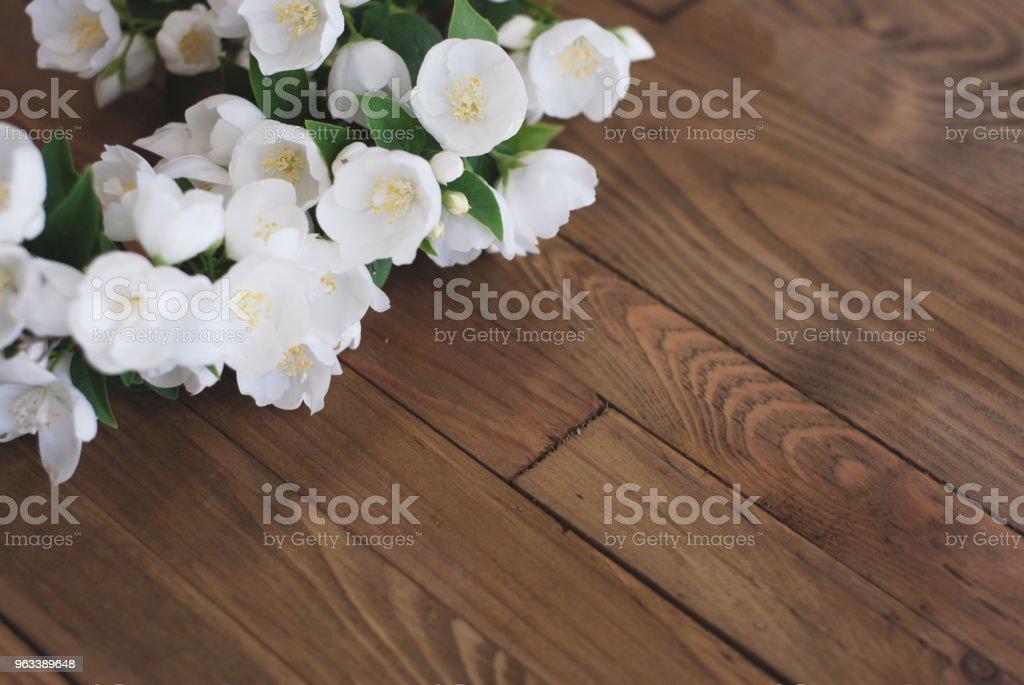 Białe kwiaty jaśminu Małe białe kwiaty na brązowym starym drewnianym tle. Miejsce na tekst. - Zbiór zdjęć royalty-free (Kwiat - Roślina)