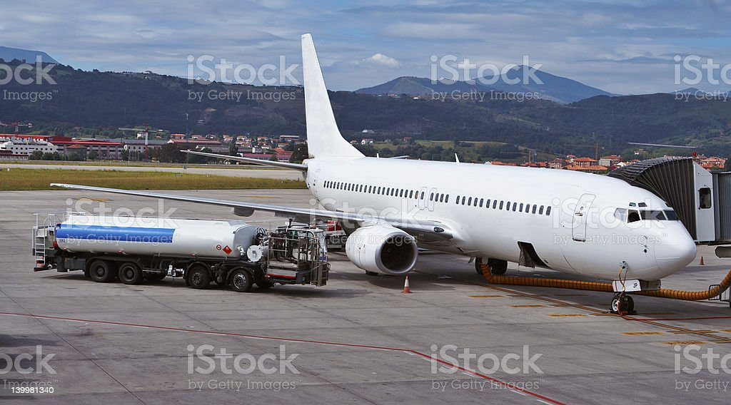 White jet plane being refueled by truck stock photo