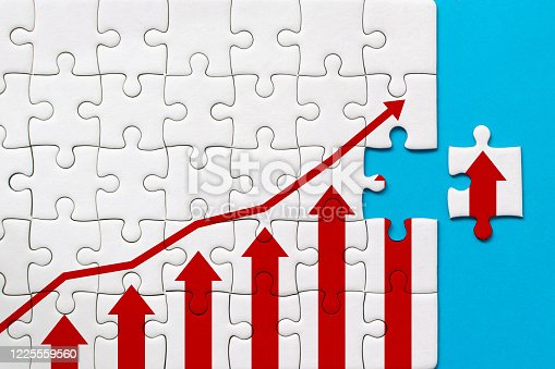 White jigsaw puzzle and graph arrow growth up on blue background. Business growth success process concept