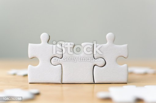 istock White jigsaw puzzle connecting together. Team business success partnership or teamwork concept 1080252288