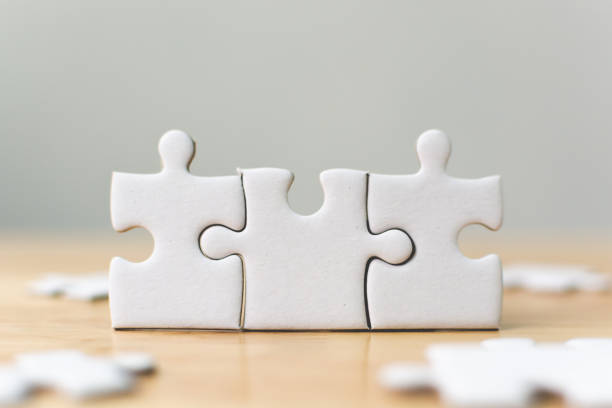 white jigsaw puzzle connecting together. team business success partnership or teamwork concept - three objects stock pictures, royalty-free photos & images
