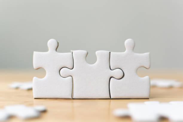 weiße jigsaw puzzle zusammenstecken. team erfolg partnerschaft oder teamarbeit geschäftskonzept - fusionen und übernahmen stock-fotos und bilder