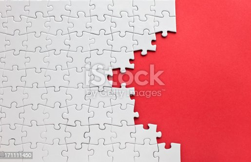 istock White jigsaw puzzle on a red background 171111450