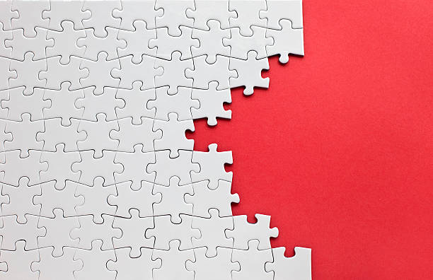 white jigsaw puzzle on a red background - jigsaw puzzle stock photos and pictures