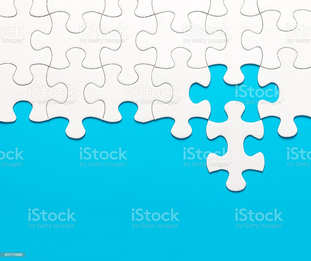 White jigsaw puzzle on blue background stock photo